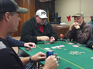 Mort Henderson and Scott Brummond (with hands folded) play a hand during weekly play of the Free Poker Network. The Eagles Club sponsors the weekly poker league in Wayne, paying for the sponsorship fee through the sale of food and drink at the club that players consume. (Photo by Michael Carnes)